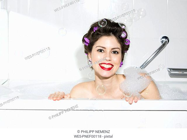Portrait of smiling young woman with curlers in bath