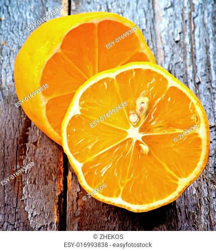 Exotic Sweet Orange Lemon Halves closeup on Rustic Wooden background