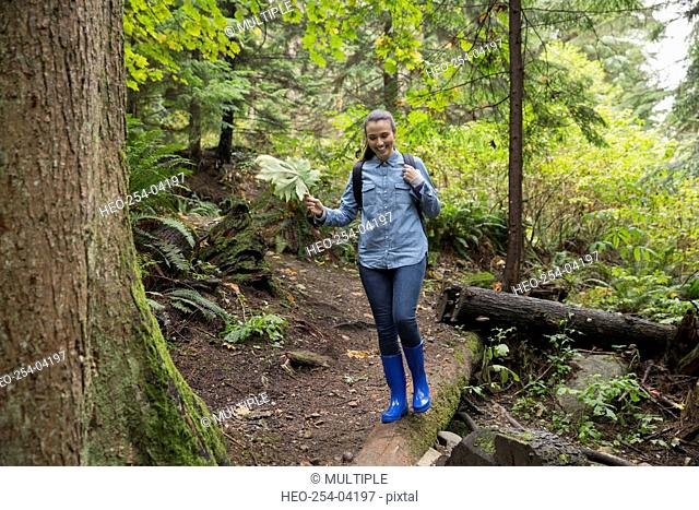 Young woman hiking on path in woods