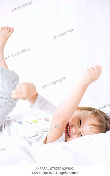 small girl having fun in bed