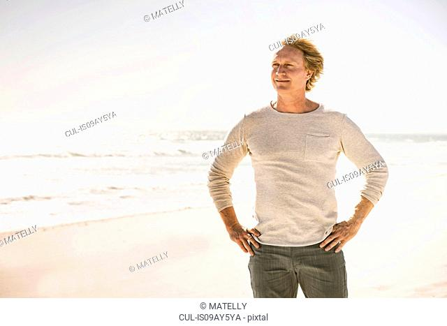 Mature man standing on beach, looking into distance