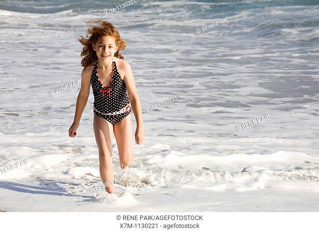 Young girl happily running through the ocean surf in Santa Cruz, California