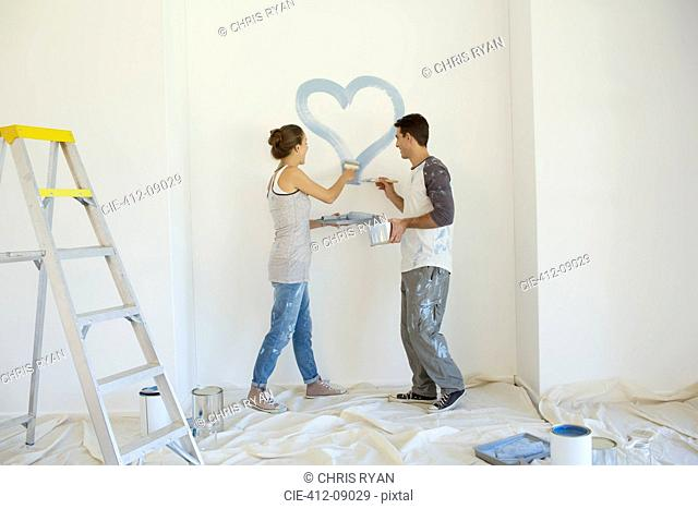 Couple painting blue heart on wall