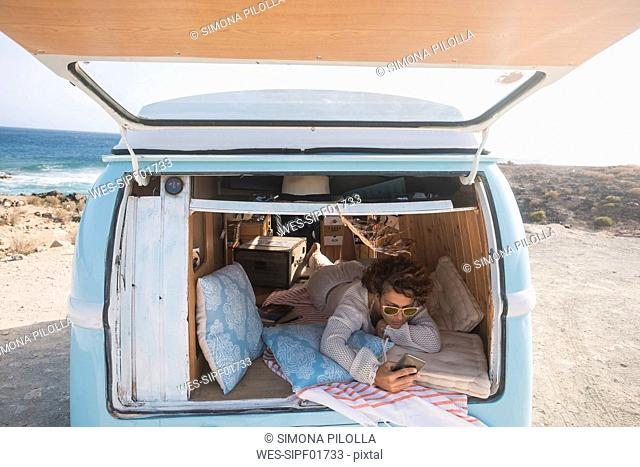 Spain, Tenerife, woman with cell phone lying in van parked at seaside