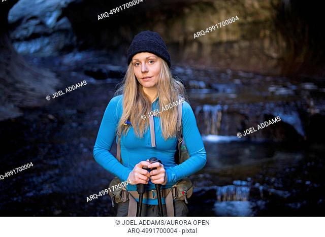 A young woman hiker pauses in the Subway in the backcountry of Zion National Park