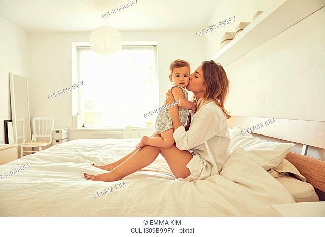 Mother sitting on bed, hugging toddler