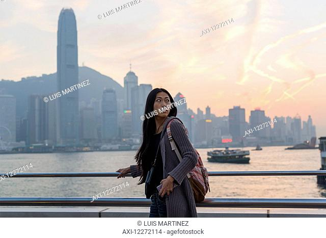 A young woman at the waterfront with a view of the skyline at sunset, Kowloon; Hong Kong, China
