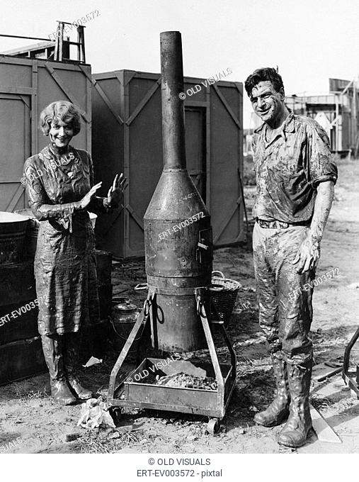 Mud covered couple with portable stove All persons depicted are not longer living and no estate exists Supplier warranties that there will be no model release...