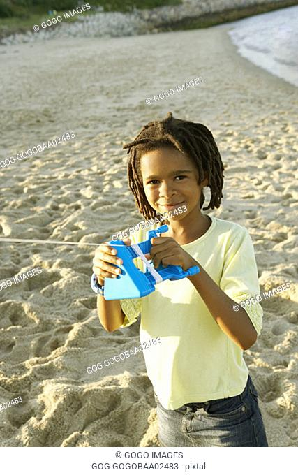 Young African boy flying a kite on beach