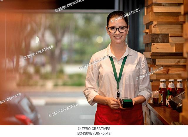 Waitress holding chip and pin machine looking at camera smiling