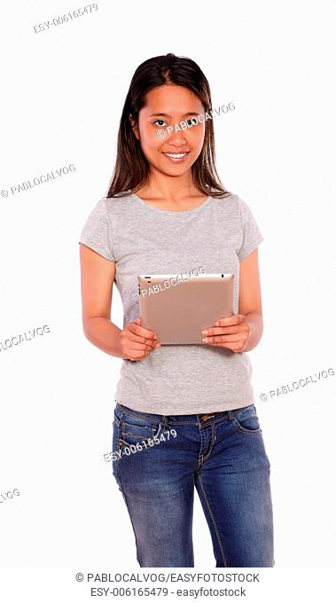 Portrait of a charming young asiatic woman looking at you and using her tablet pc on blue jeans on isolated background