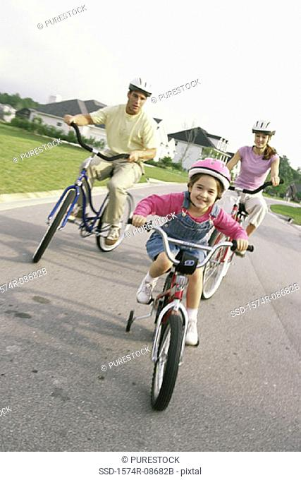 Daughter cycling with her parents