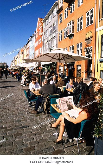 Nyhavn. Houses and restaurants. Quayside. Cafe. Coffee shop. blue sky. newspaper. relaxing