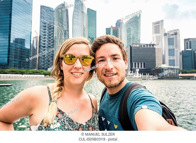Tourists posing in front of Singapore skyline, Marina Bay
