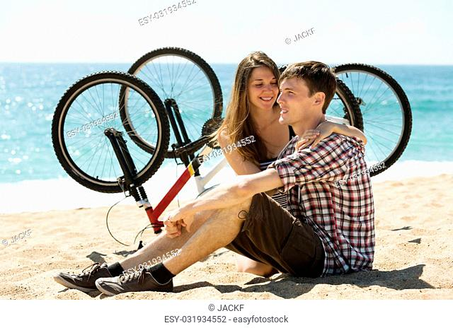 Young lovers with bikes resting on beach at sunny day