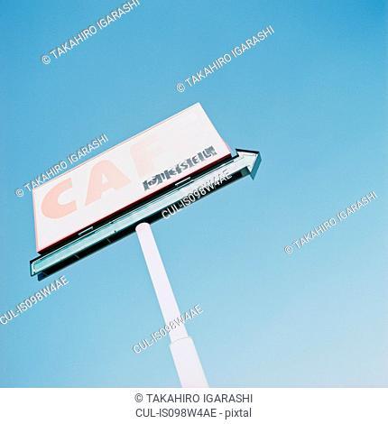 Cafe sign against blue sky