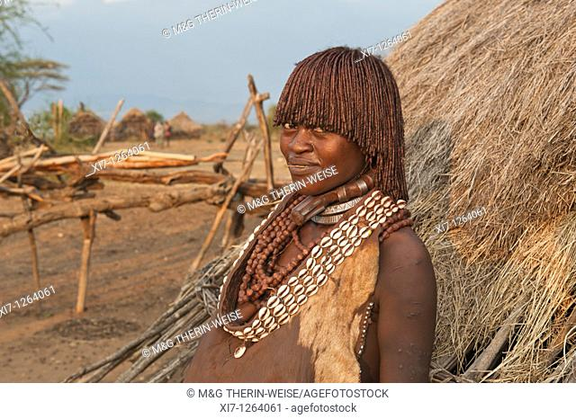 Pregnant Hamar woman with necklaces made of Cowry shells in front of her wooden hut, Omo river valley, Southern Ethiopia