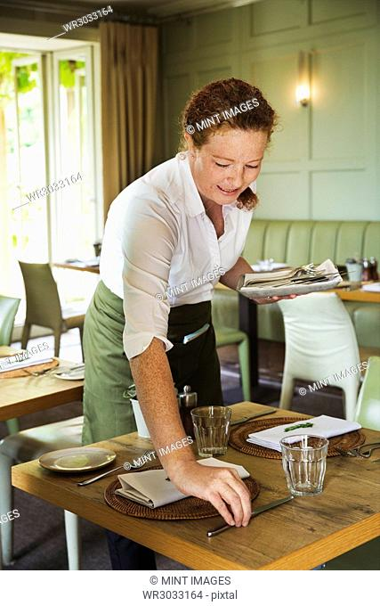 Woman wearing apron setting table in a restaurant