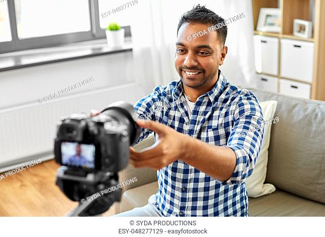indian male video blogger adjusting camera at home