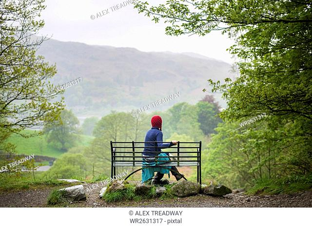 A woman rests on a bench while walking in The Lake District near Grasmere, Cumbria, England, United Kingdom, Europe