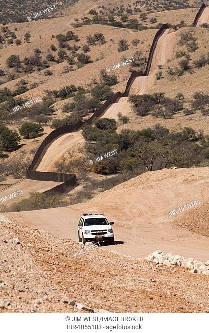 A US Border Patrol vehicle patrols the fence that separates the United States and Mexico in the Sonoran Desert west of Nogales, Arizona, USA