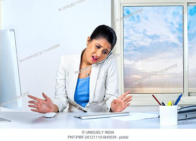 Businesswoman looking upset while talking on a mobile phone in an office