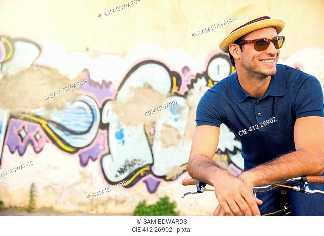 Smiling man in hat and sunglasses leaning on bicycle next to urban graffiti wall
