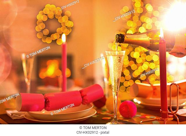 Pouring champagne into champagne flute on Christmas dinner table with Christmas cracker