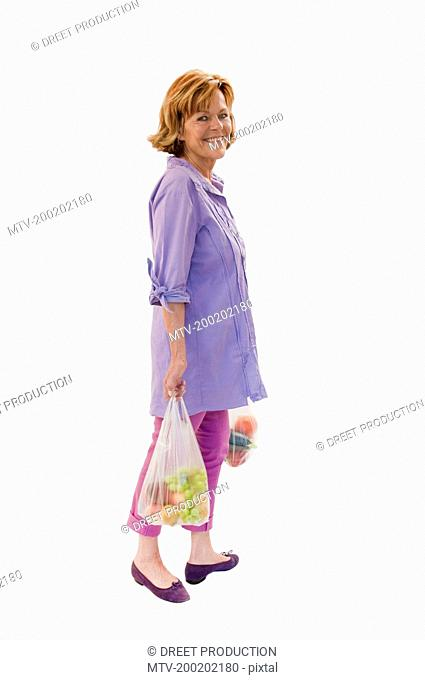 Senior woman holding fruits and vegetables in plastic bag, smiling, portrait