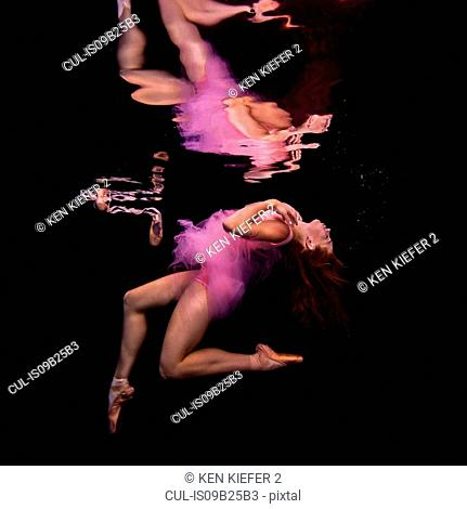 Underwater view of girl wearing tutu and ballet shoes, floating towards water surface