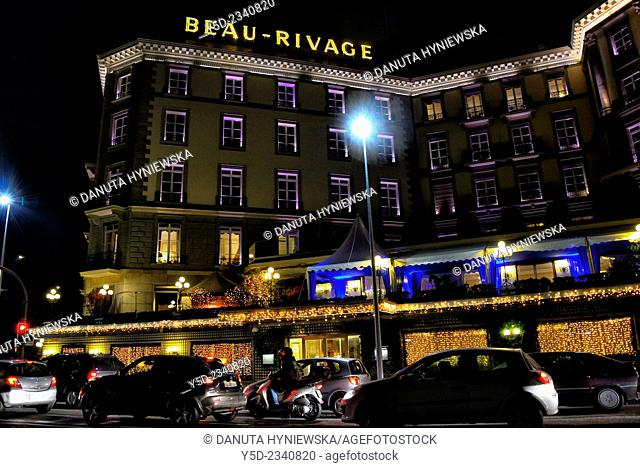 Quai du Mont -Blanc along Lake Geneva by night, Five-star luxury historic hotel Beau-Rivage in foreground, Geneva, Switzerland