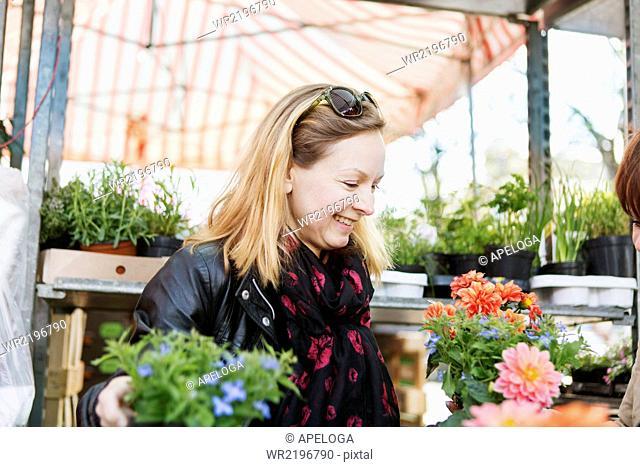 Happy mature woman buying flower plants in nursery