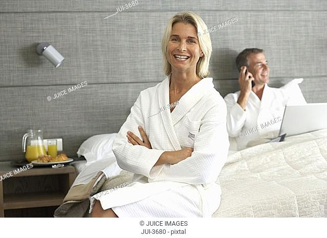 Couple in bathrobes sitting on hotel bed, man using laptop and mobile phone, woman smiling