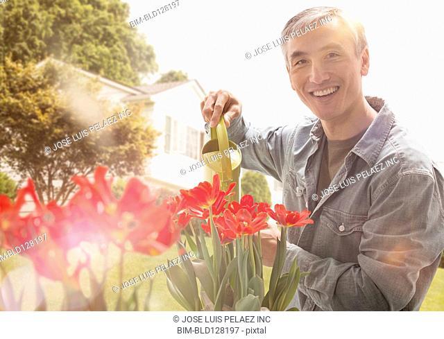 Chinese man watering flowers in garden