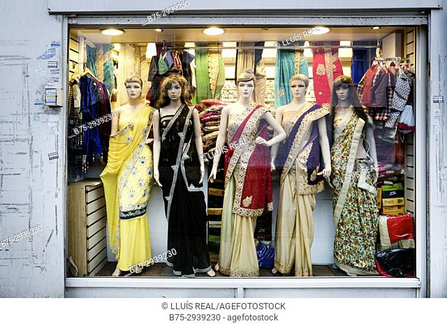 Indian fashion store. Shop window with female mannequins in Indian clothes. Glass reflections. London, England