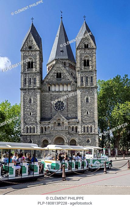 Tourists in little tourist train in front of the Temple neuf, Neo-Romanesque Protestant Reformed Church in the city Metz, Moselle, Lorraine, France