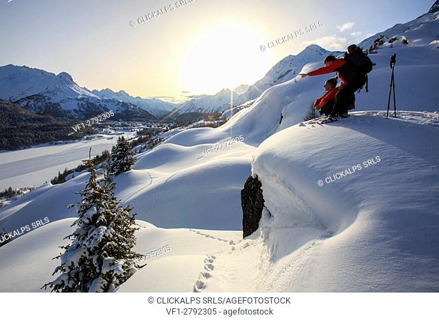 Hikers with snowshoes observe the sun set to the Maloja Pass. Engadine. Switzerland. Europe