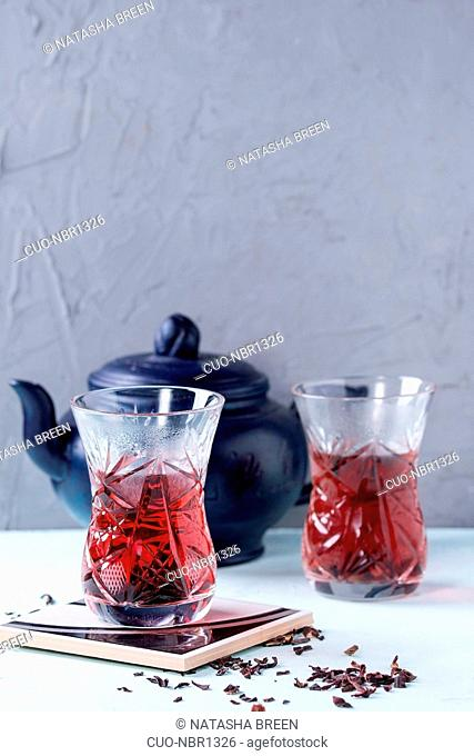 Two traditional asian style glasses with hibiscus tea karkade, served with dry hibiskus and dark blue ceramic teapot over blue and gray textured background