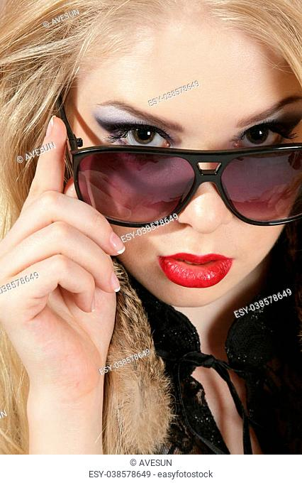 Young blond woman portrait looking over dark sunglasses