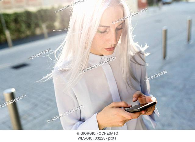 Young businesswoman checking cell phone in the city