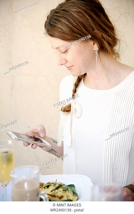 Portrait of a woman with long auburn hair in a braid, looking at her cell phone