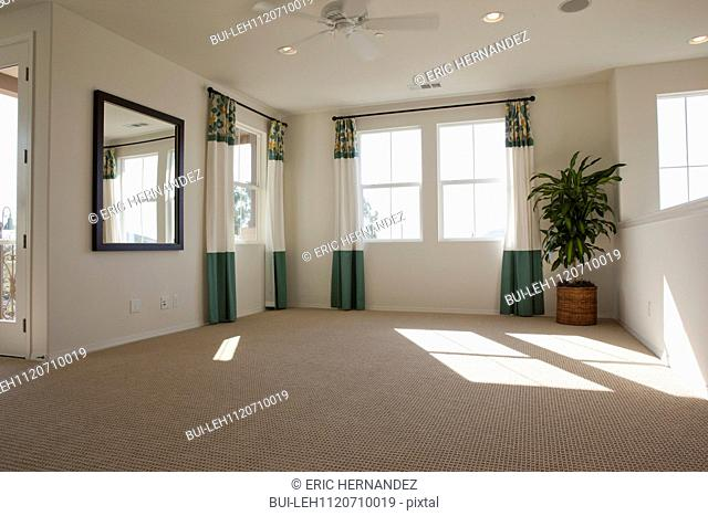 Empty room with carpet on floor and curtains on windows at home; San Marcos; California; USA