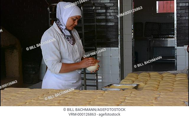 Tangier Morocco local woman baking bread in kitchen and oven