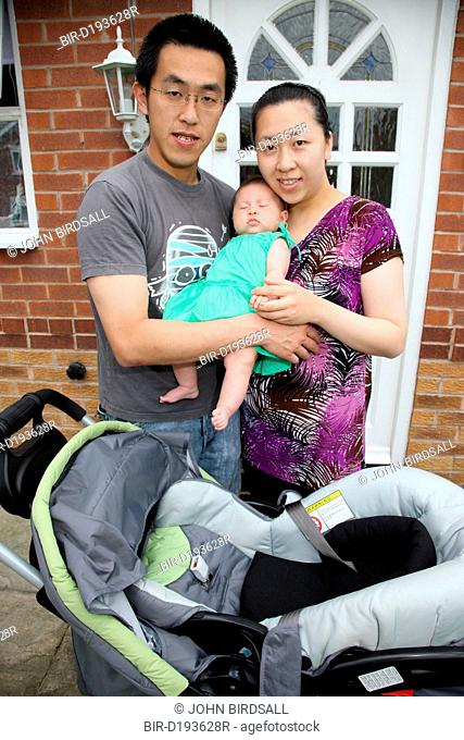 Chinese parents with baby at their front door
