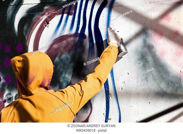 man in hood paint graffiti