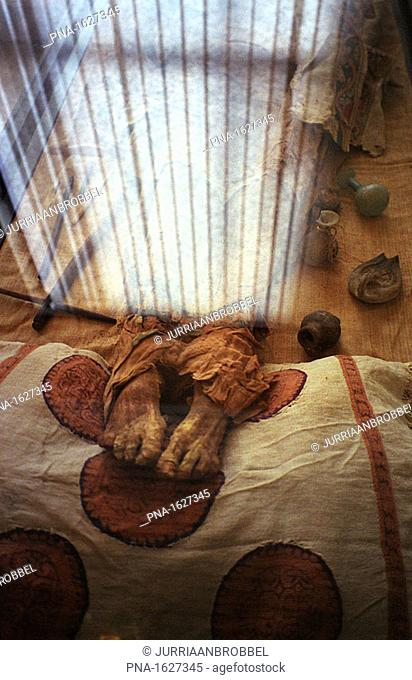 Egyptian mummy's feet underneath the reflection of a window inside the National Historical Museum of Brussels, Belgium