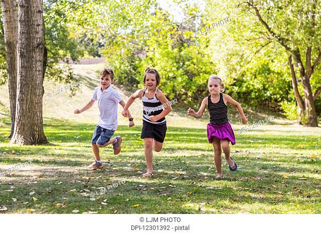 Three siblings racing in a park; Edmonton, Alberta, Canada