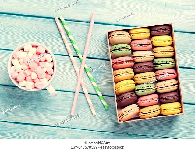 Colorful macaroons and coffee cup with marshmallow on wooden table. Sweet macarons in gift box. Toned