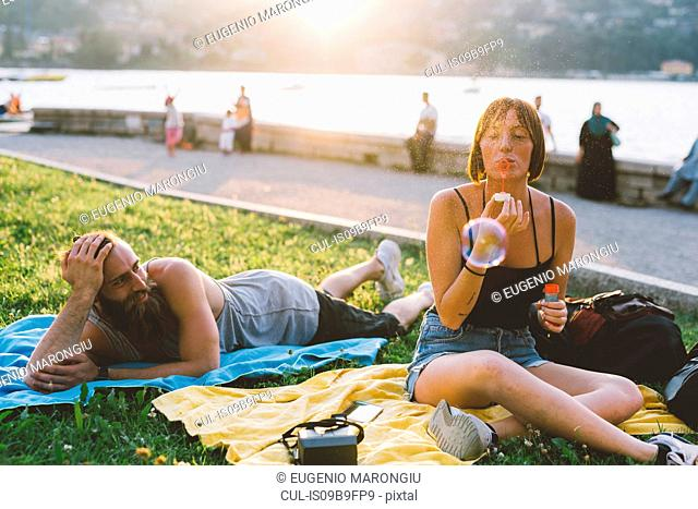 Young couple blowing bubbles on waterfront grass, Lake Como, Lombardy, Italy