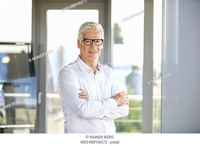 Confident businessman standing in office, with arms crossed